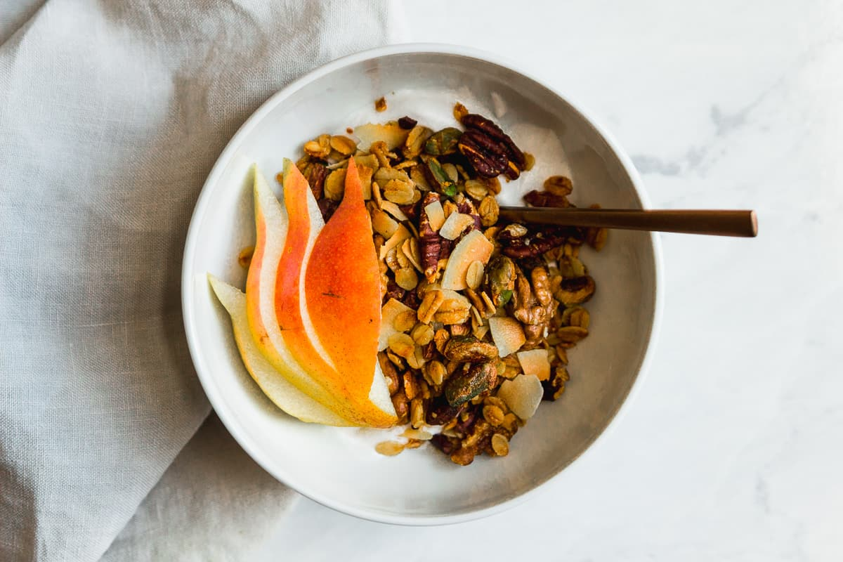 granola with yogurt and pear in a bowl