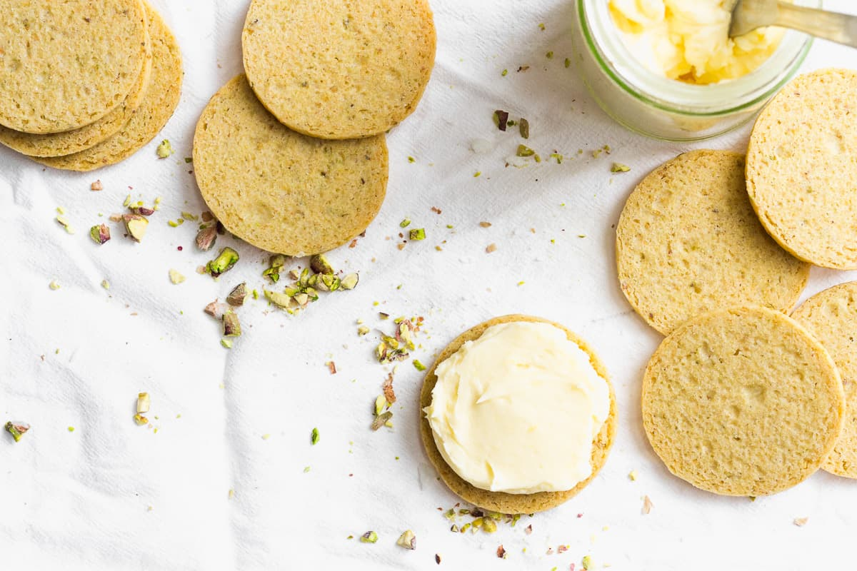 Pistachio and Lemon Cream Sandwich Cookies Being Iced