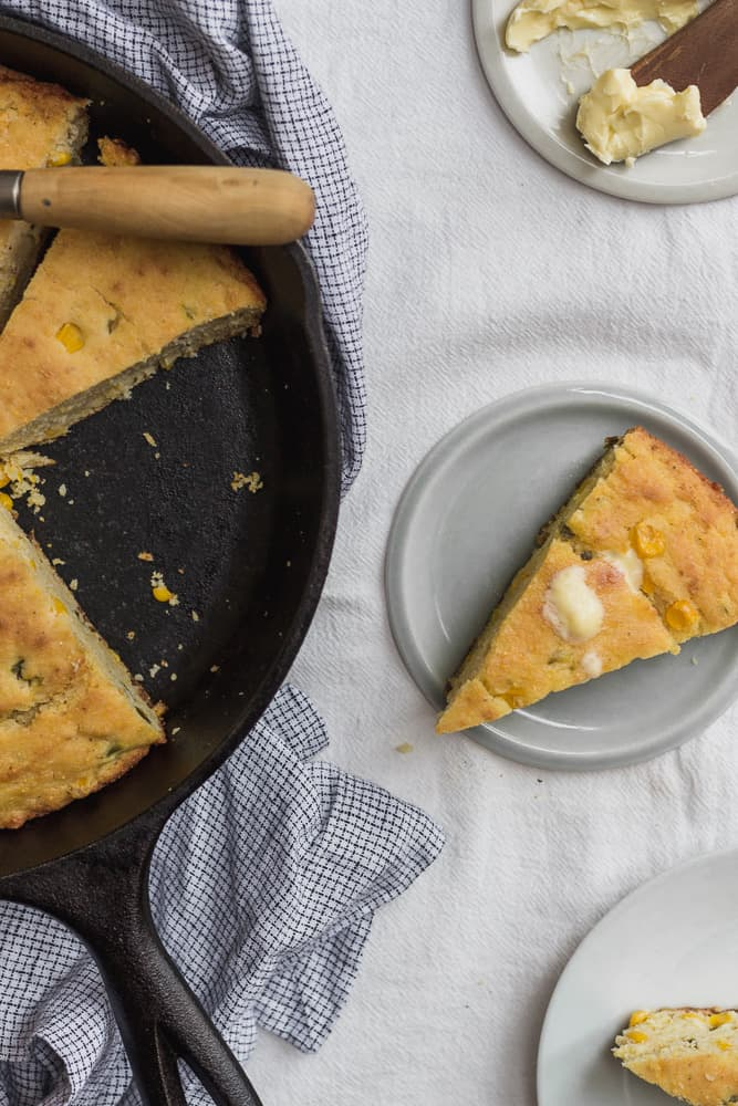 Slice of Cornbread next to Cornbread in Cast-Iron Skillet