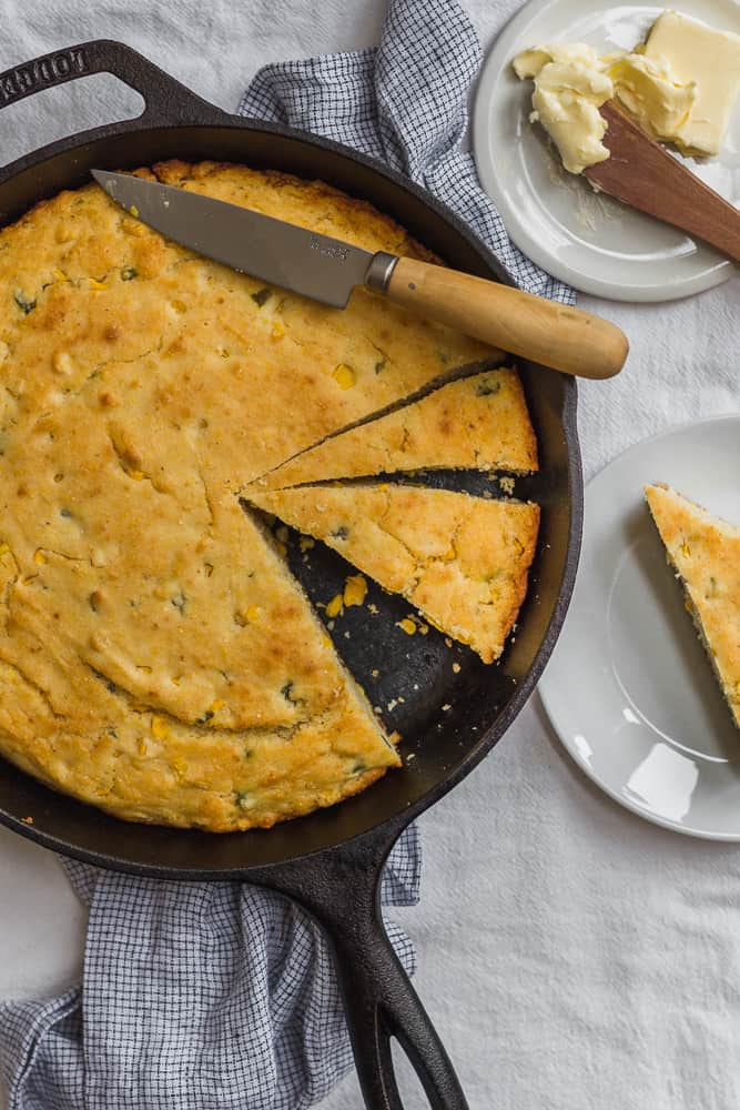 Slices of Cornbread in Cast-Iron Skillet with Butter