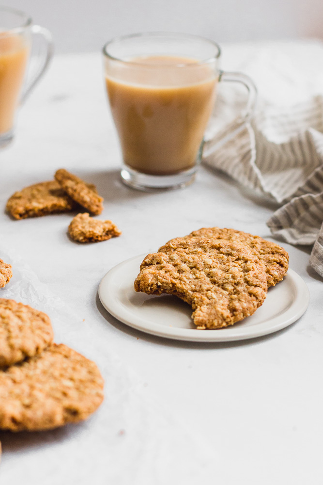 hobnobs on a plate with a bite taken out and a cup of tea