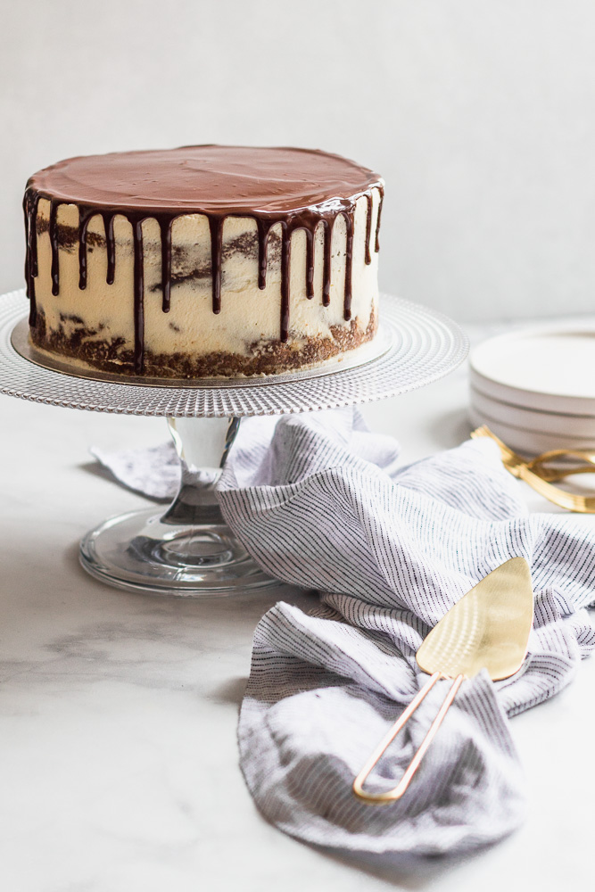 maple stout layer cake on a cake stand with a cake server and linen
